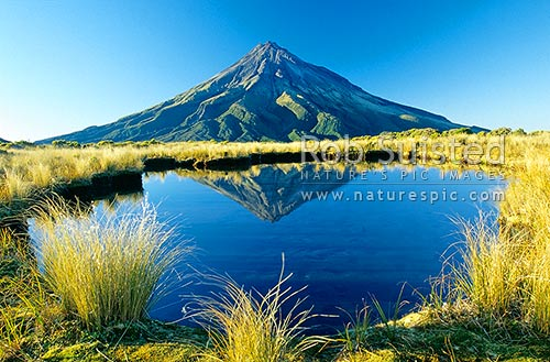 Mount (Mt) Egmont/Taranaki (2518m) reflected in a mountain tarn on the Pouakai Range, Egmont National Park, Taranaki, New Plymouth District, Taranaki Region, New Zealand (NZ) stock photo.
