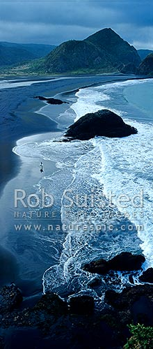 Surf rolling onto Whatipu Beach (black ironsand) at the entrance to Manukau harbour. Surfer leaving the sea, Auckland, Waitakere City District, Auckland Region, New Zealand (NZ) stock photo.