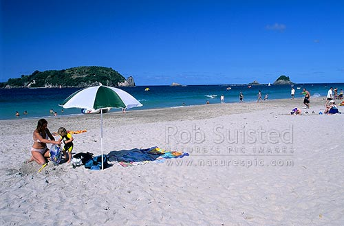 People enjoying Hahei beach. Mahurangi Island (L) and Te Karaka Island far right. Woman and girl under beach umbrella in foreground, Coromandel Peninsula, Thames-Coromandel District, Waikato Region, New Zealand (NZ) stock photo.