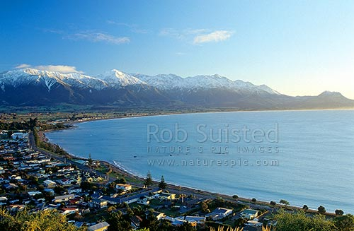 Kaikoura township at dawn. Snow covered Seaward Kaikoura Range and Mount (Mt) Fyffe beyond, Kaikoura, Kaikoura District, Canterbury Region, New Zealand (NZ) stock photo.