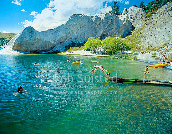 Summer swimming in Blue Lake, St Bathans. Lake formed from old gold sluicing operations late 1800, St Bathans, Central Otago District, Otago Region, New Zealand (NZ) stock photo.