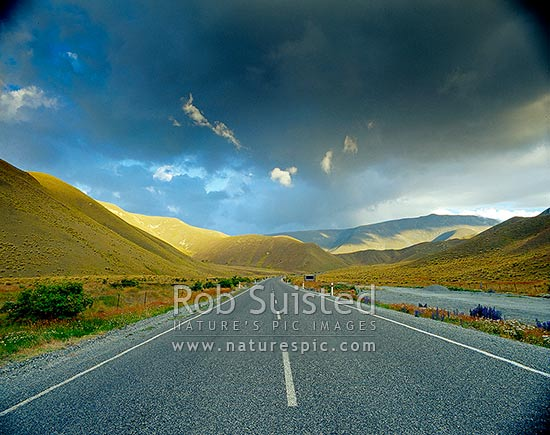 Soft evening light on tussock country - Lindis Pass road, Lindis Pass, MacKenzie District, Canterbury Region, New Zealand (NZ) stock photo.