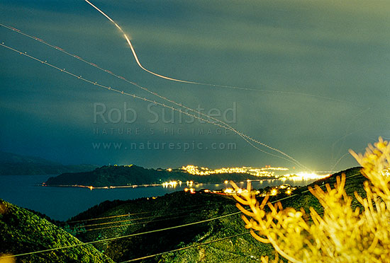 Night shot of Wellington harbour and airport with plane tracks or trails in sky, Wellington, Wellington City District, Wellington Region, New Zealand (NZ) stock photo.