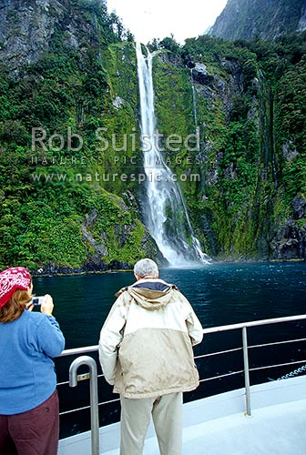 Tourists enjoying the Real Journey's scenic tour on Milford Sound. Stirling Falls waterfall, Fiordland National Park, Southland District, Southland Region, New Zealand (NZ) stock photo.