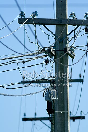 Tangle of telephone wires, power lines and cable TV cables on power pole, New Zealand (NZ) stock photo.
