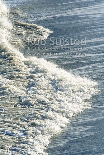 Waves surging up the sloping sandy beach at Cape Palliser, Cape Palliser, New Zealand (NZ) stock photo.
