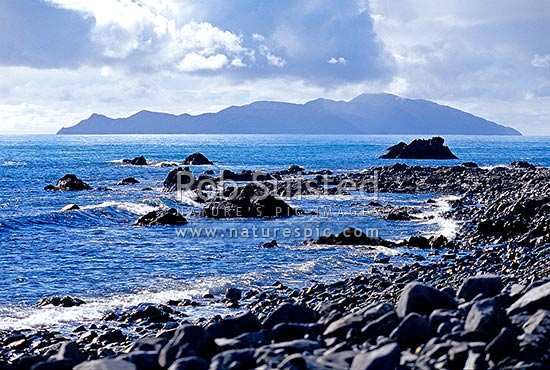 Kapiti Island from rocky coast near Pukerua Bay, Pukerua Bay, Porirua City District, Wellington Region, New Zealand (NZ) stock photo.