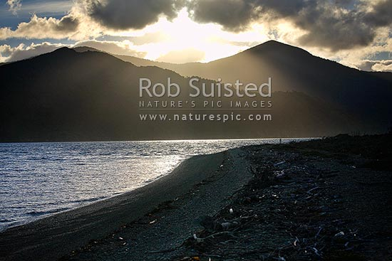 Sun filtering down past Mount Furneaux (823m) onto Queen Charlotte Sound and the beach on Long Island, Marlborough Sounds, Marlborough District, Marlborough Region, New Zealand (NZ) stock photo.