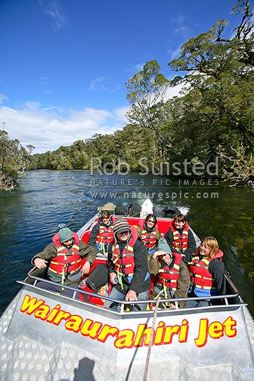 Johan Groters driving tourist visitors in the W-Jet boat trip through a gentle section of the upper Wairaurahiri River, Waitutu Forest, Fiordland, Southland District, Southland Region, New Zealand (NZ) stock photo.