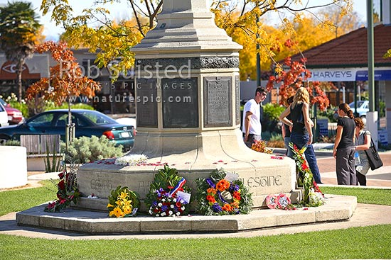 Havelock North War memorial statue tower and plaques, with flower wreaths from ANZAC day commemorations, Havelock North, Hastings District, Hawke's Bay Region, New Zealand (NZ) stock photo.