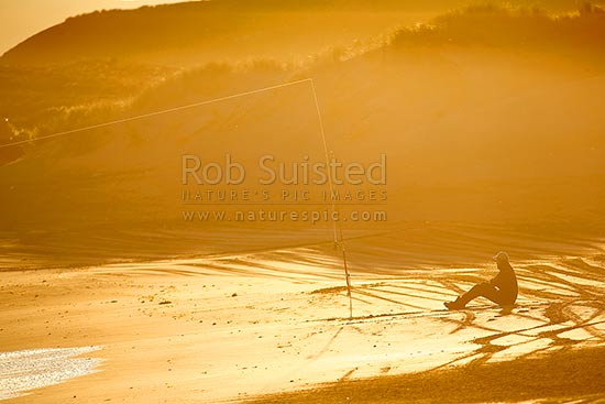 Recreational fishermen surfcasting fishing from beach in late evening light, Masterton District, Wellington Region, New Zealand (NZ) stock photo.
