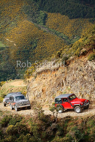 4WD 4x4 four wheel drive vehicles climbing a steep twisting rocky gravel road or track, Wellington City District, Wellington Region, New Zealand (NZ) stock photo.