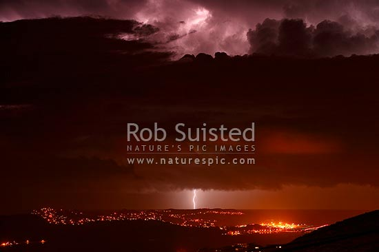 Fork lightning strike over Wellington Airport and Miramar Peninsula at night with approaching southerly front. Cloud-to-ground lightning, Wellington, Wellington City District, Wellington Region, New Zealand (NZ) stock photo.