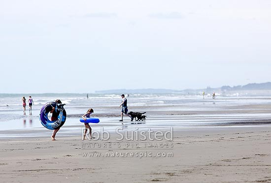 People walking on beach with inflatable toys and man walking dog., Peka Peka Beach, Kapiti Coast District, Wellington Region, New Zealand (NZ) stock photo.