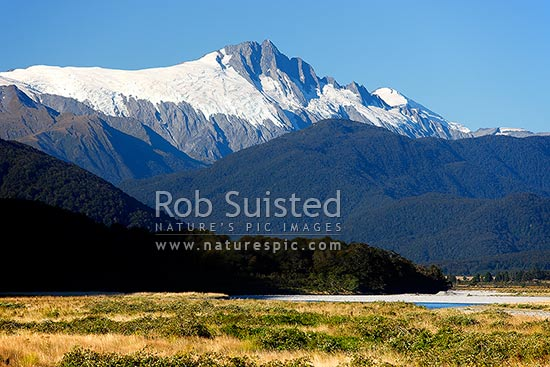 Mount (Mt) Hooker (2652m centre) and Clarkes Mound (1105m below Hooker) above the Haast River flats, Haast, Westland District, West Coast Region, New Zealand (NZ) stock photo.