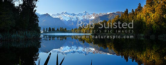 Lake Matheson. Morning calm reflections on lake with Aoraki / Mount Cook (right;3754m) and Mount Tasman (left;3498m). Morning mist. Panorama, Westland National Park, Westland District, West Coast Region, New Zealand (NZ) stock photo.
