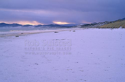Snow on the beach. Masons Bay, Stewart Island. Mid winter, Stewart Island, Stewart Island District, Southland Region, New Zealand (NZ) stock photo.