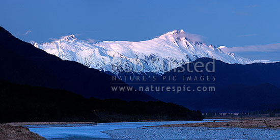 Mount Hooker (2652m centre) Mt Cullaugh (2286m left) above the Haast and Landsborough Rivers at dusk in winter. Panorama, Haast, Westland District, West Coast Region, New Zealand (NZ) stock photo.