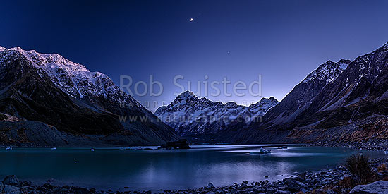 Aoraki / Mount Cook (3754m) above Hooker Lake and Hooker Glacier. Pre-dawn with moon above. Icebergs and bergy bits floating on lake. Panorama, Aoraki / Mount Cook National Park, MacKenzie District, Canterbury Region, New Zealand (NZ) stock photo.
