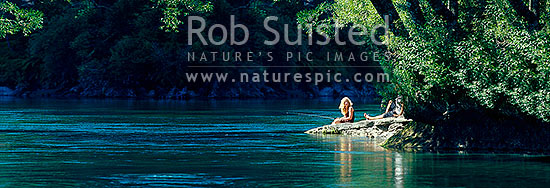 Relaxing sunny summer's day fishing on the Waikato River. Young woman and friend trout fishing under willow trees. Panorama, Taupo, Taupo District, Waikato Region, New Zealand (NZ) stock photo.