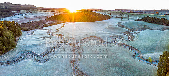 Balls Clearing Scenic Reserve and Clifton Conservation Area at dawn with heavy frost, as sun rises over hill. Headwaters of Mangatutu Stream. Aerial panorama, Puketitiri, Hastings District, Hawke's Bay Region, New Zealand (NZ) stock photo.